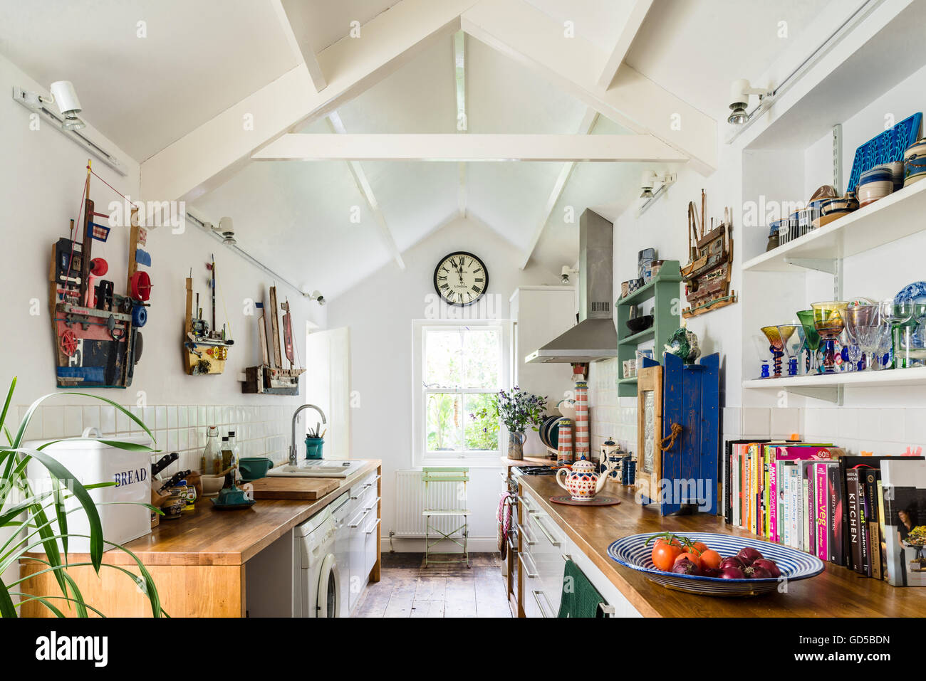 Galley style white kitchen with pitched roof, wooden worktops and ...