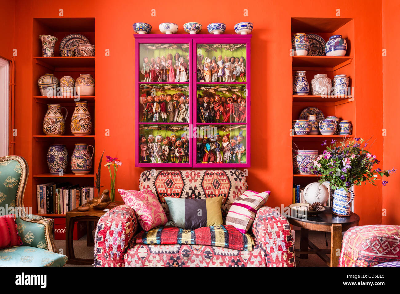 Club sofa upholstered in kilim material beneath glass-fronted pink cabinet containing collection of marionette puppets. - Stock Image