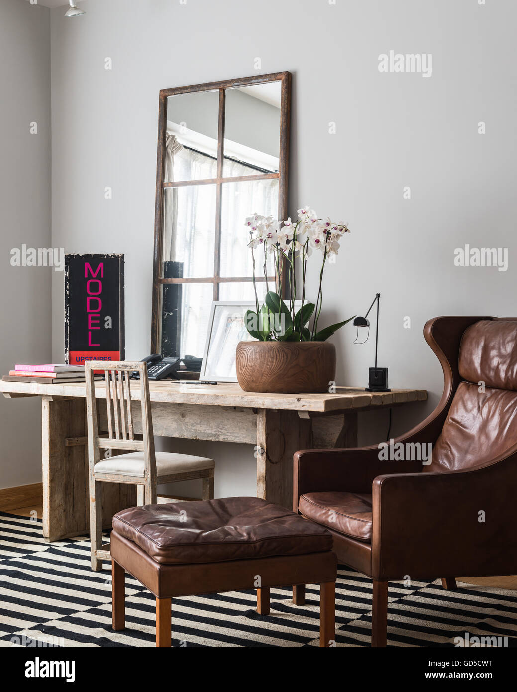Wood pot of orchids on rustic wooden table in sitting room with panelled mirror and wing back leather armchair Stock Photo