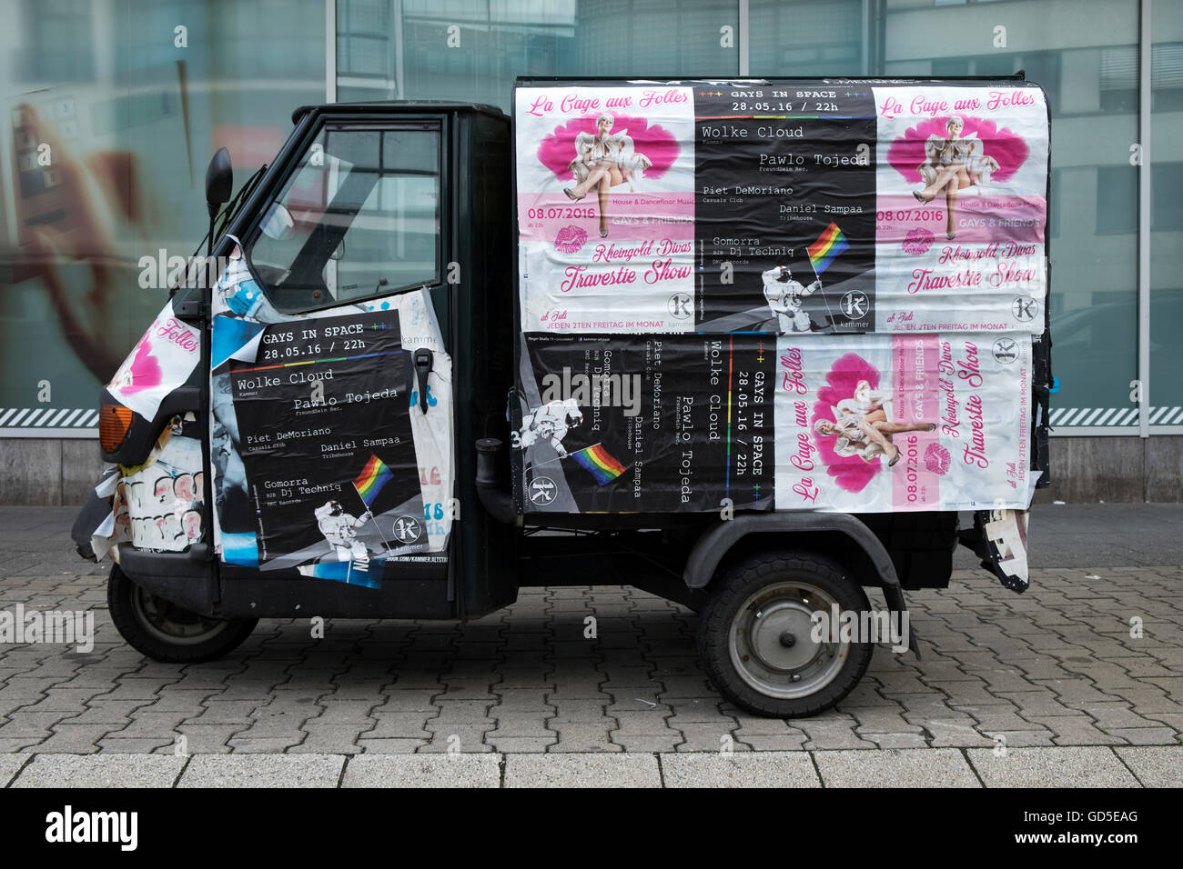 Three-Wheeled commercial delivery van covered in flyers advertising Gay nightclubs and events, Dusseldorf, Germany, - Stock Image
