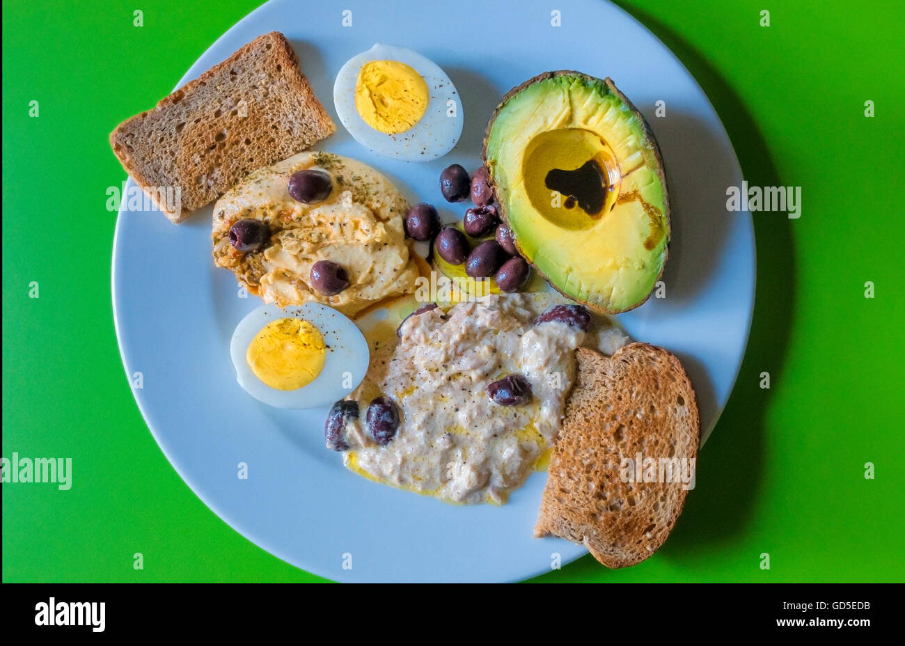 Cold food: hard-boiled egg, humus, tuna salad, olives, whole wheat toast - Stock Image