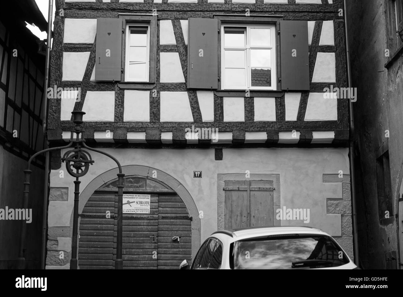 Old well pulley wheel and modern new car, riquewihr colmar, france, europe Stock Photo