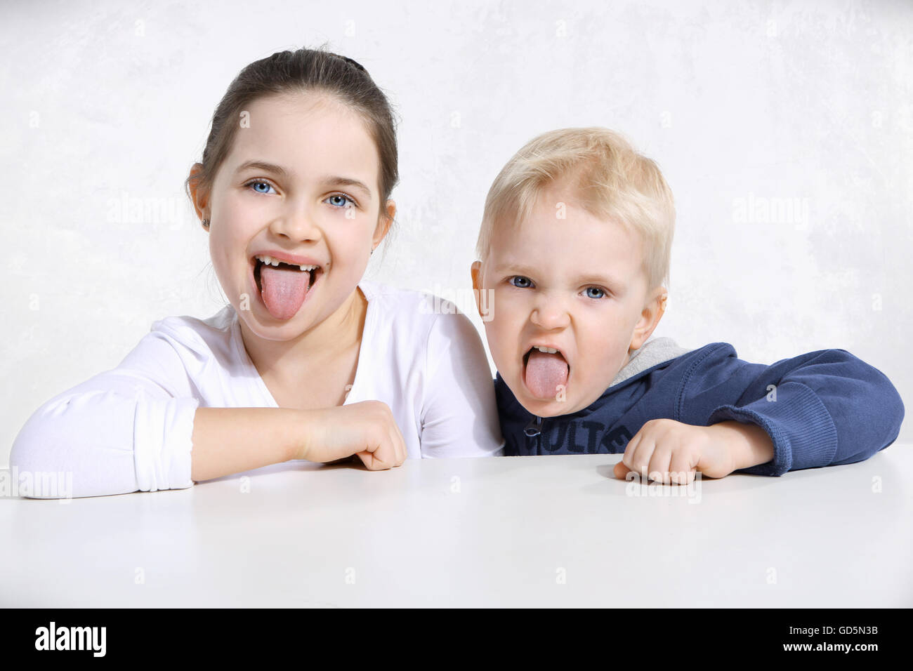 Brother and sister stick out tongues - Stock Image