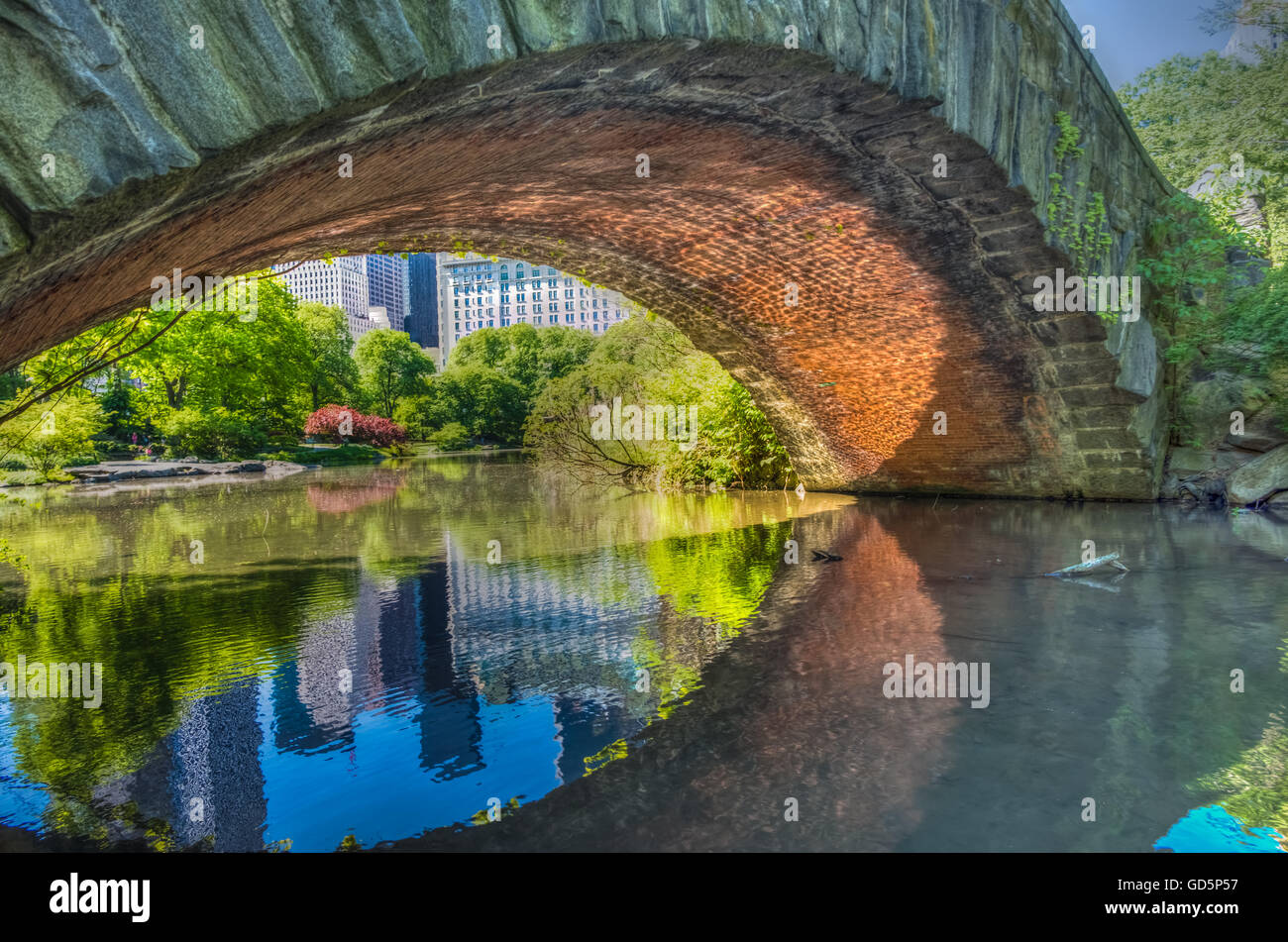 Gapstow Bridge arch reflected on the Central park pond, New York, NY - Stock Image