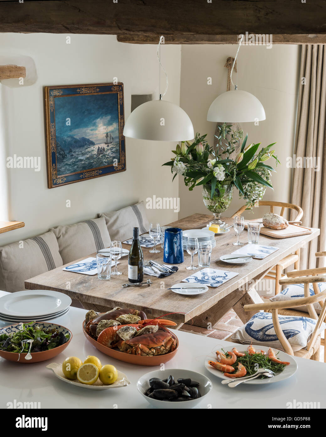 Seafood feast laid out on worktop by laid dining table - Stock Image