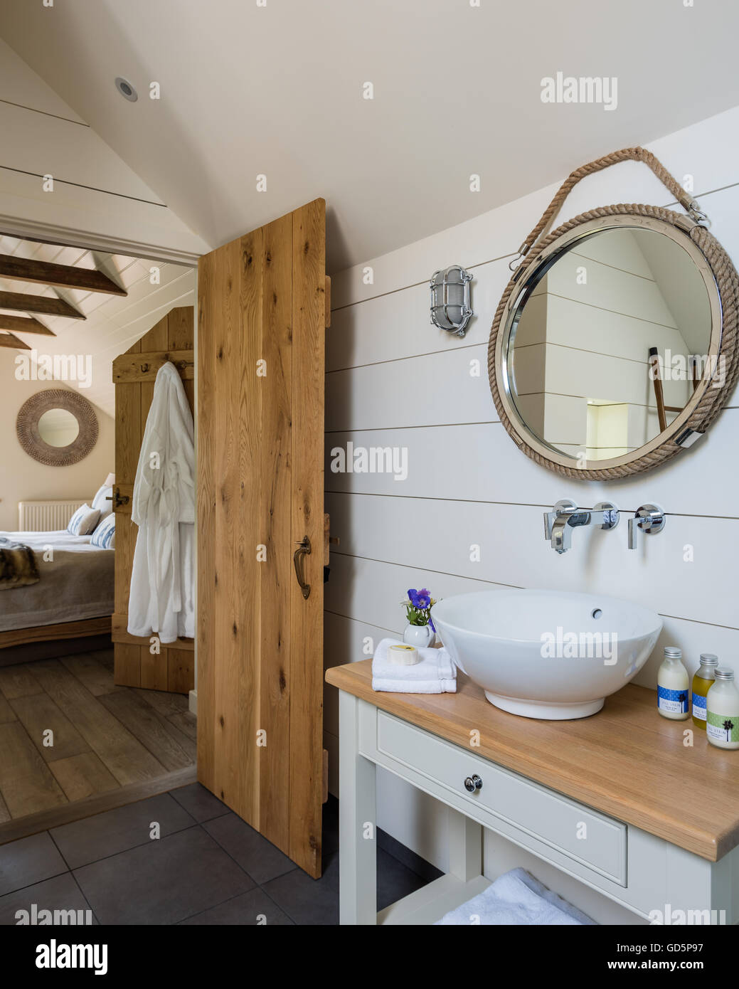 Painted white wooden planks and nautical style mirror in ensuite bathroom - Stock Image