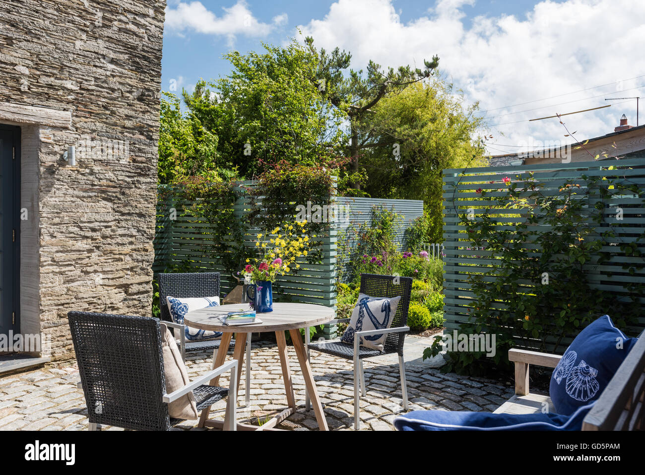Garden furniture in cottage courtyard with circular brick paver patio - Stock Image