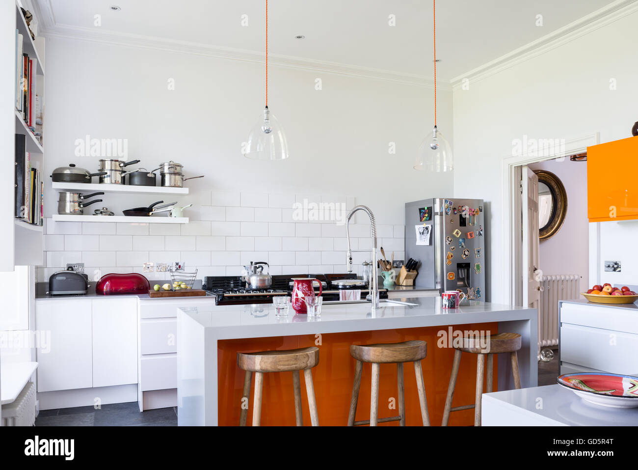 Wooden bar stools in high ceilinged kitchen with white metro tiles. The clear glass dome lights are from Baileys - Stock Image