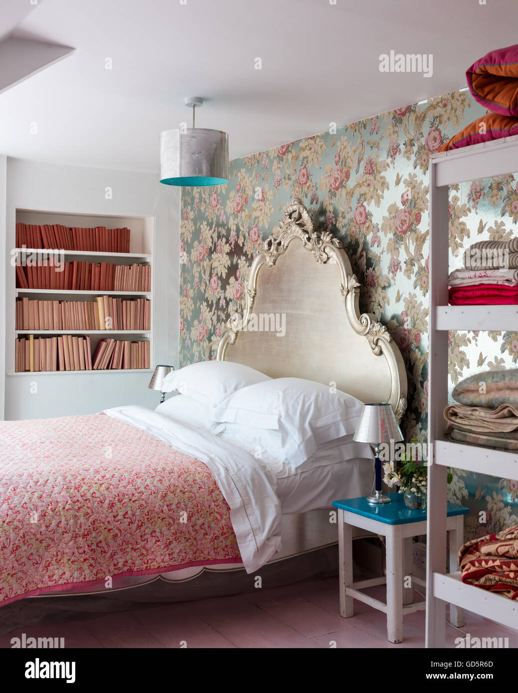 Silver foil floral wallpaper by Anna French in bedroom with ornate carved silverleaf bed and vintage french quilt. - Stock Image