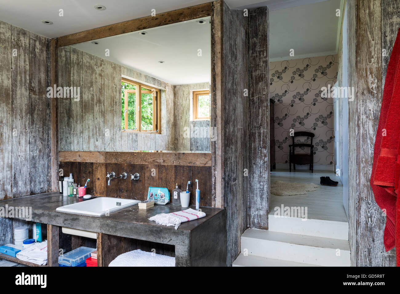 Polished concrete vanity unit in ensuite bathroom with walls lined with recycled floorboards Stock Photo