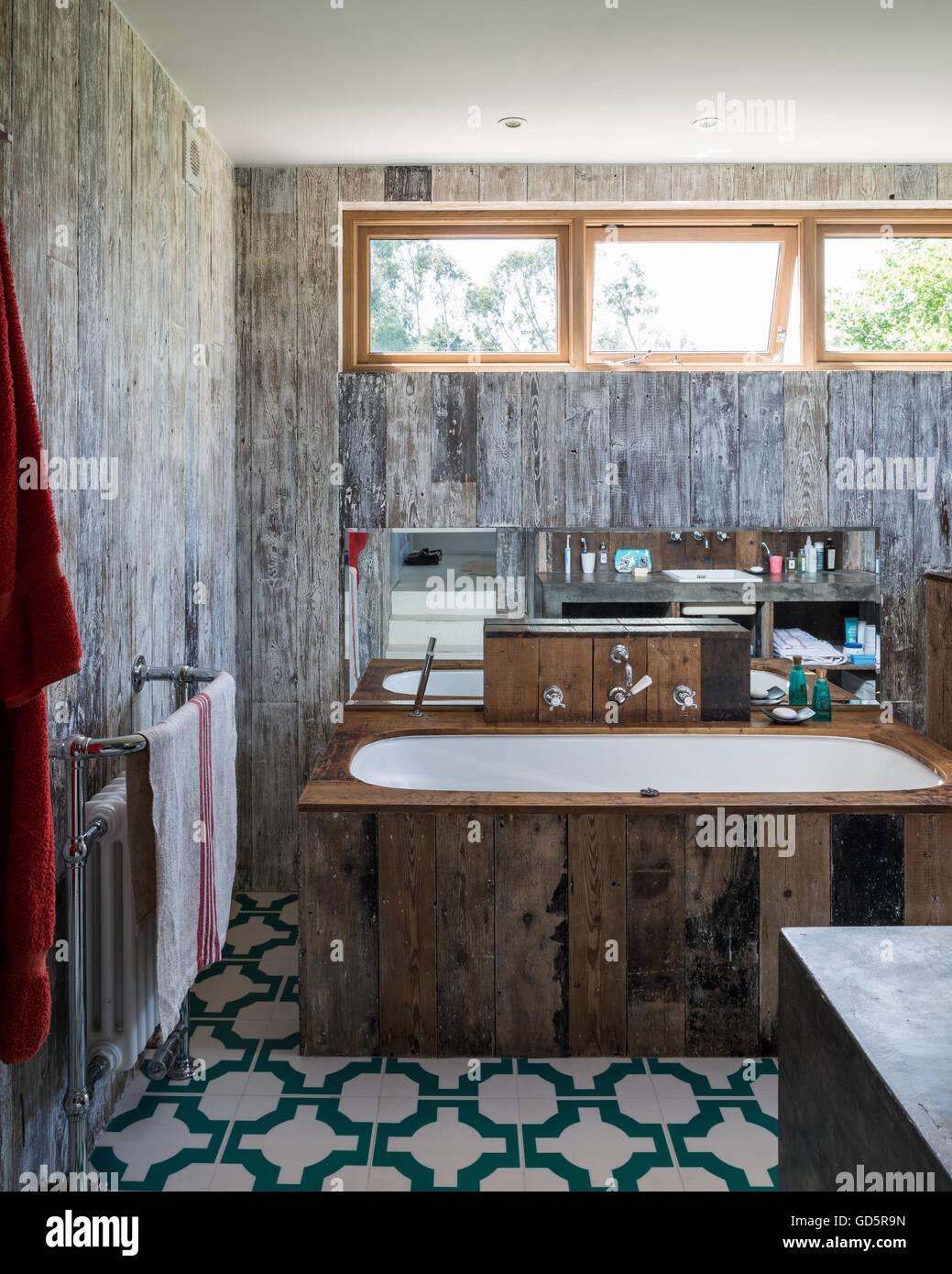 Bath tub clad in recycled floorboards in bathroom with Parquet Turquoise vinyl floor tiles by Neisha Crosland - Stock Image