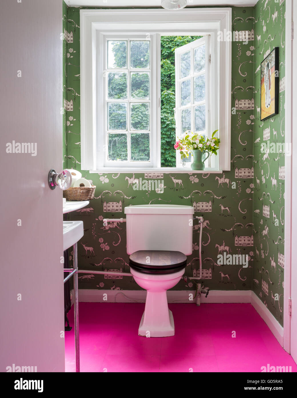 Vibrant pink tiled floor in cloakroom with green toilet wallpaper - Stock Image