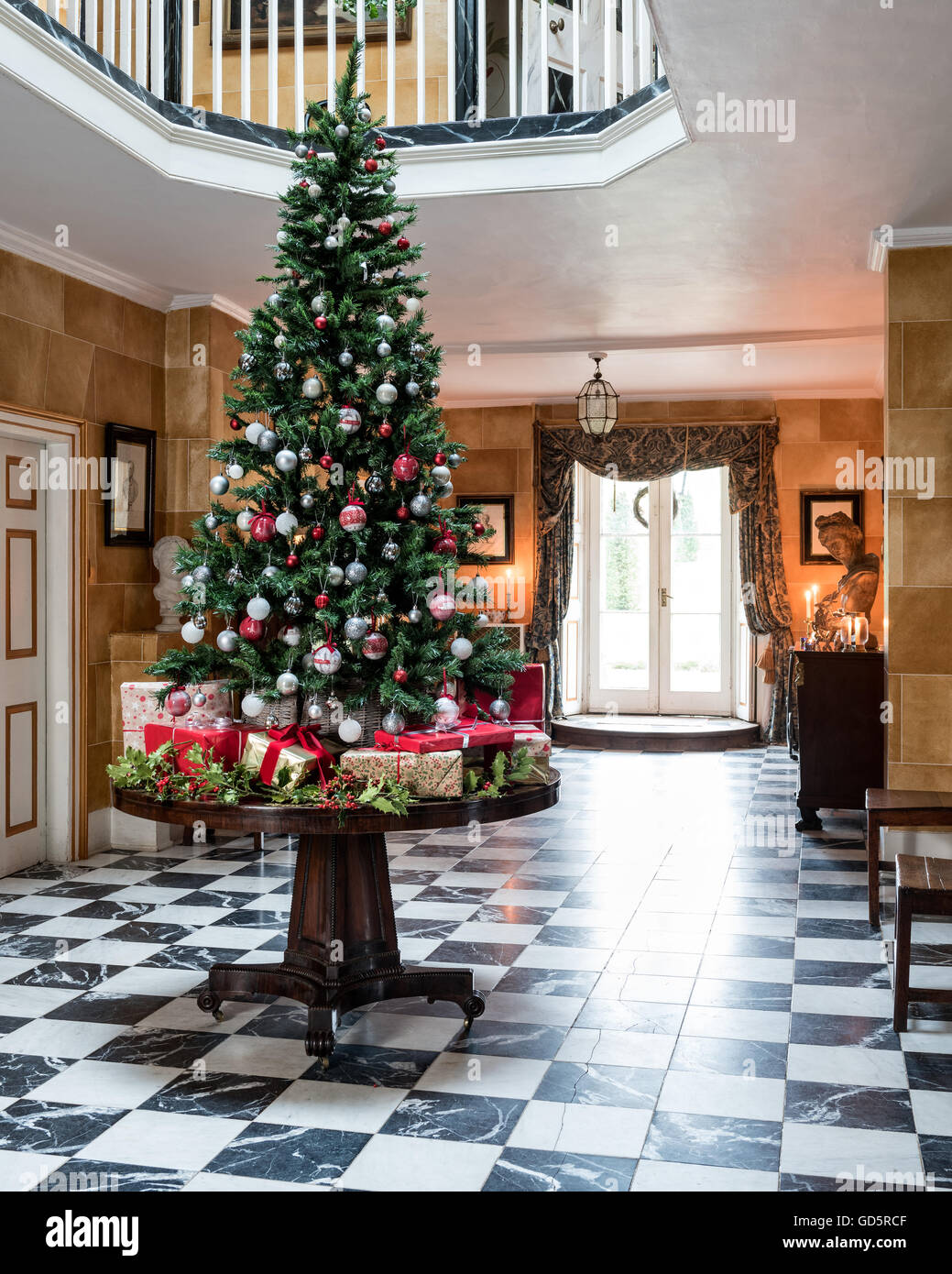 Christmas tree on wooden table with pedestal base in entrance hall of Surrey Rectory, England, UK - Stock Image