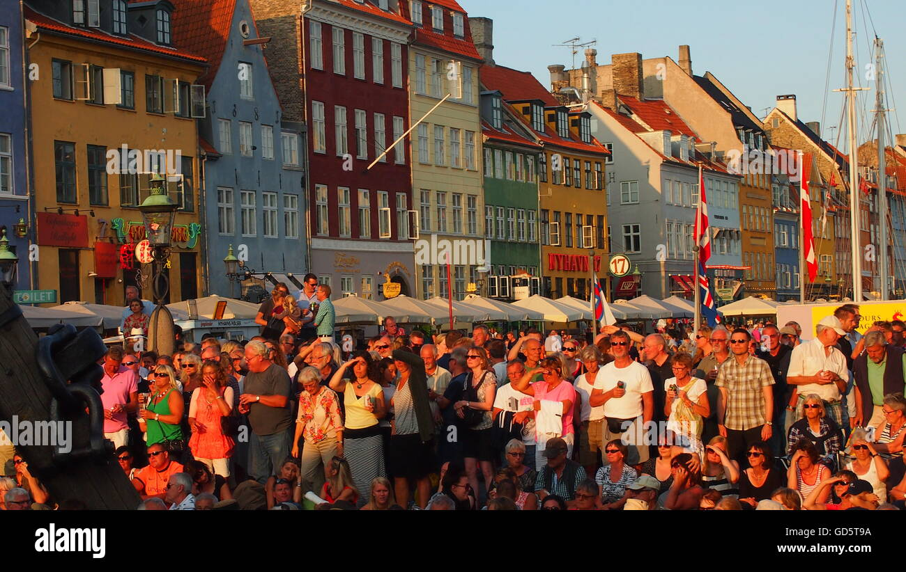 Copenhagen, Denmark – July 12th, 2013: A large crowd watching live music and dancing at sunset in the famous Nyhavn - Stock Image