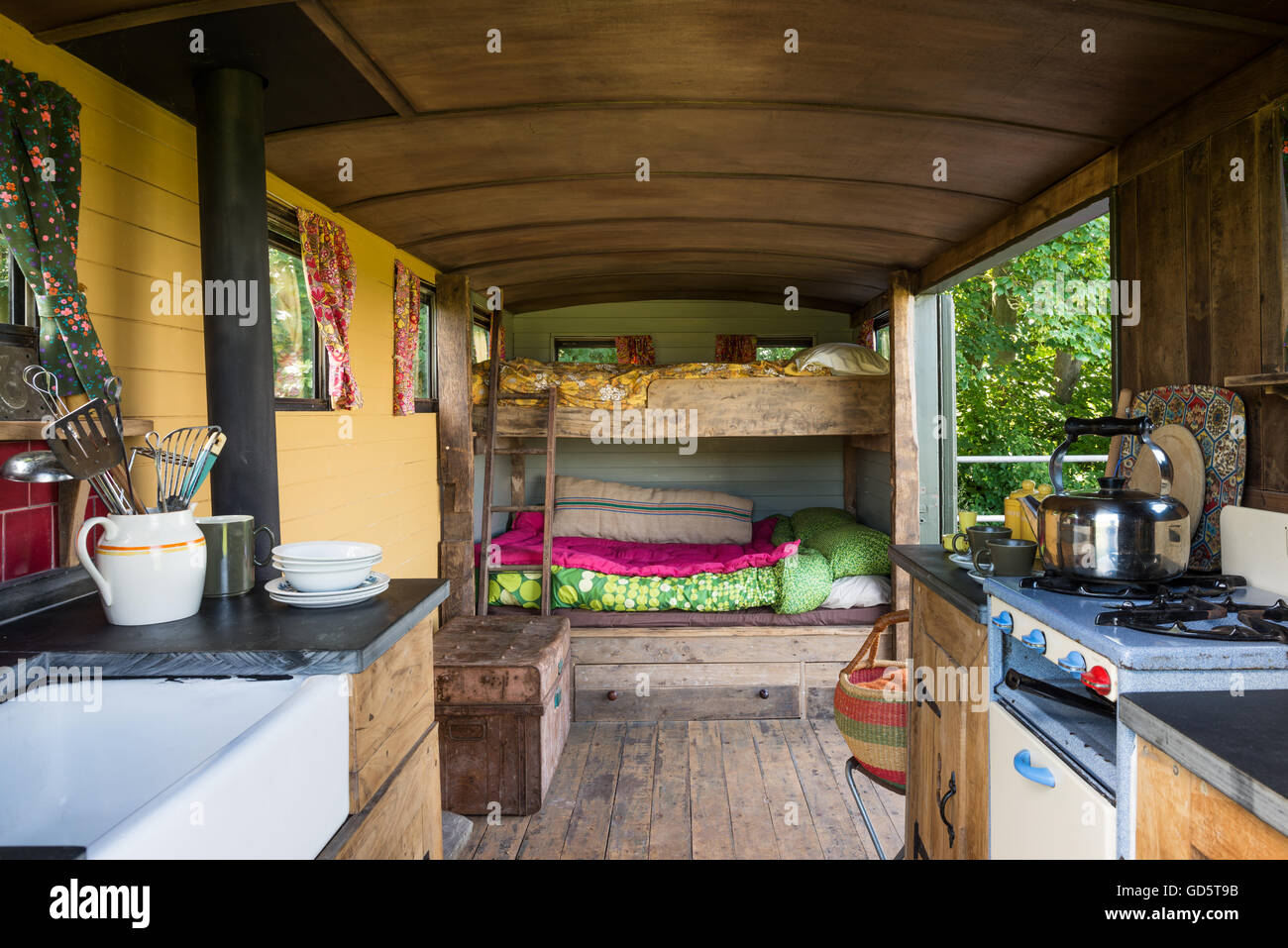 Interior of converted Brockhouse military wagon hut with wood cladding; slate worktops and wood burning stove. - Stock Image