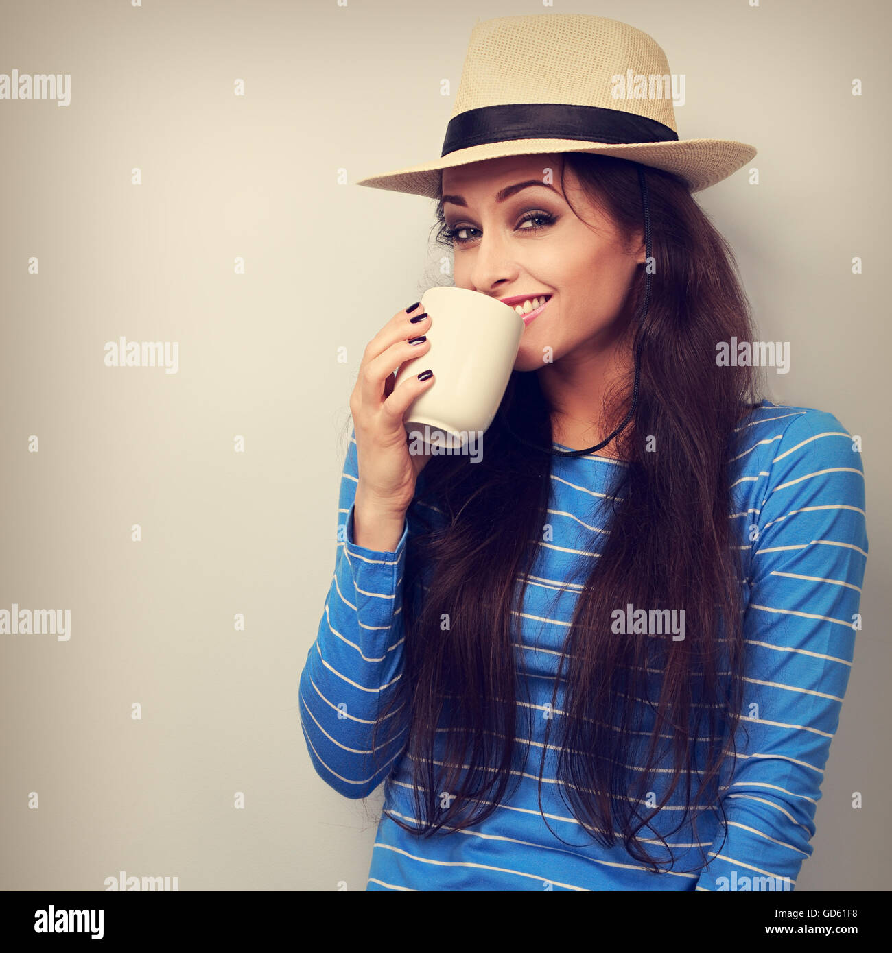 Happy woman in straw hat drinking coffee with fun emotional face. Toned closeup portrait - Stock Image