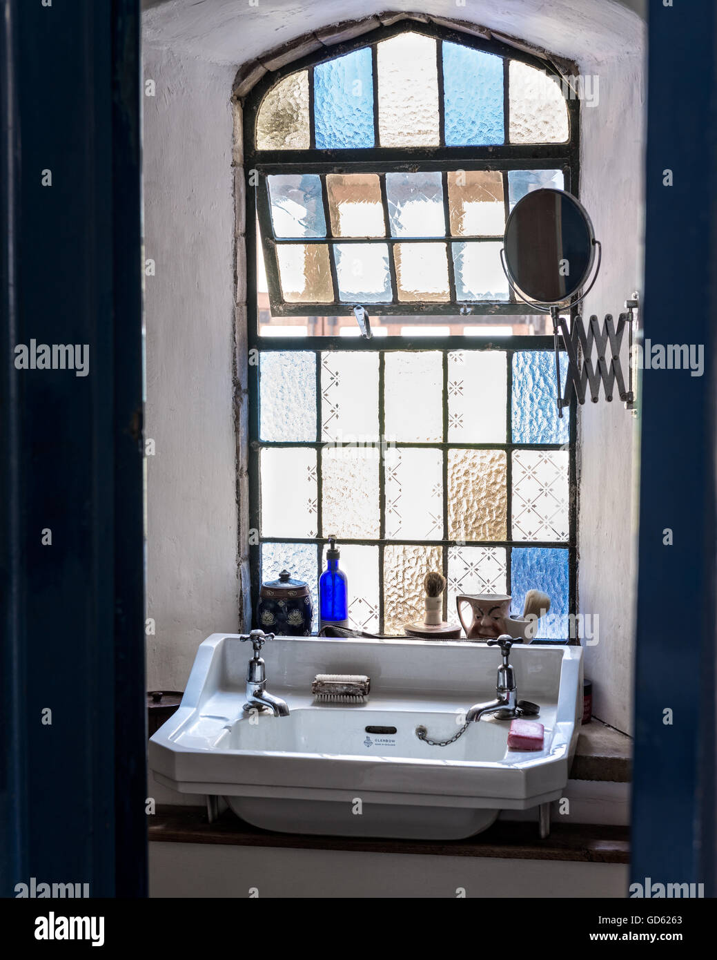 Stained glass and lead lights in arched window of bathroom - Stock Image