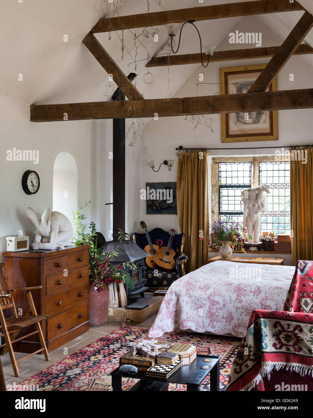 Bright kelim in airy bedroom with ceilings beams, woodburning stove and Sophie ryder sculptures Stock Photo