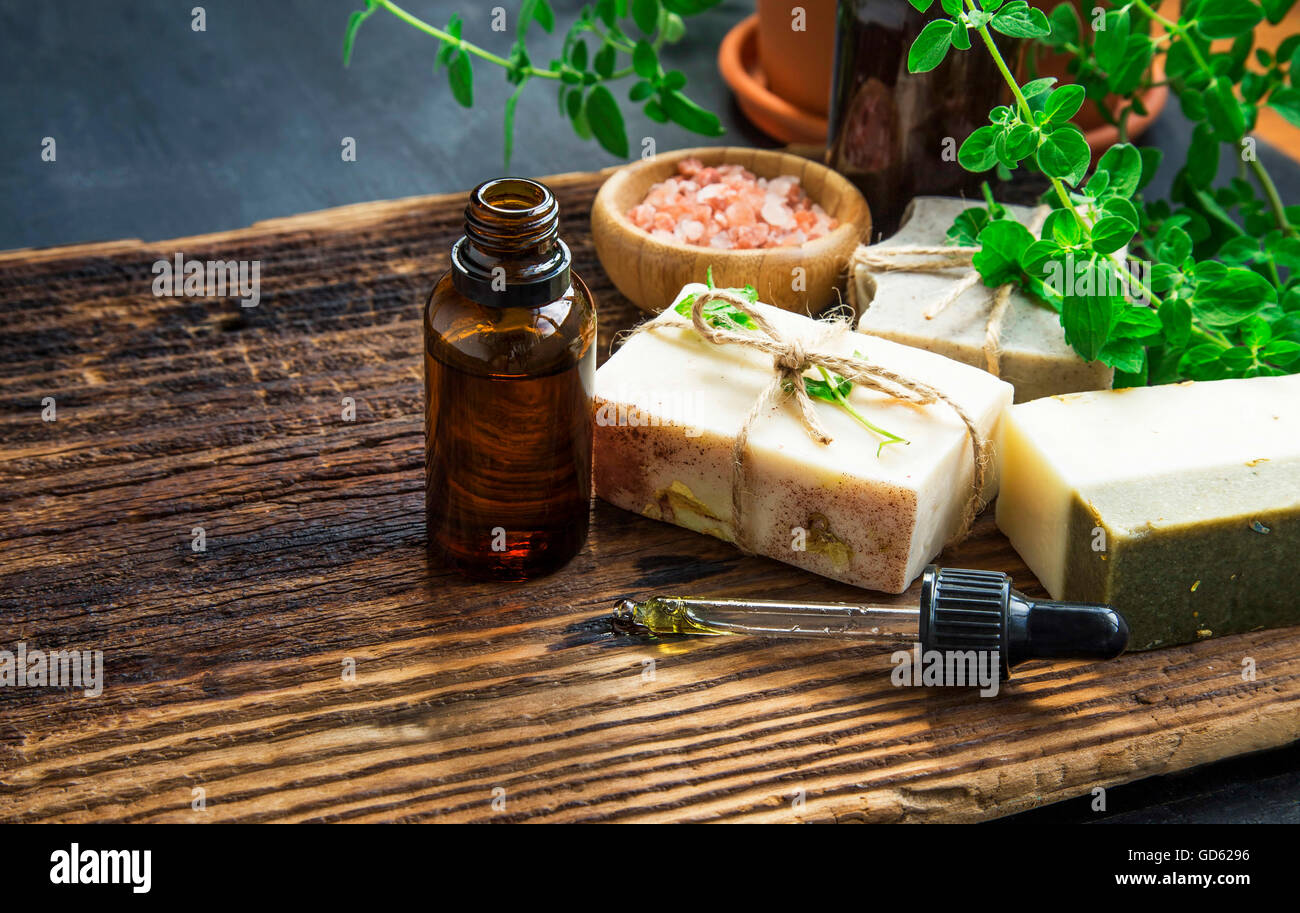 Herbal spa therapy with body oil, natural soap, salt and green herb - Stock Image