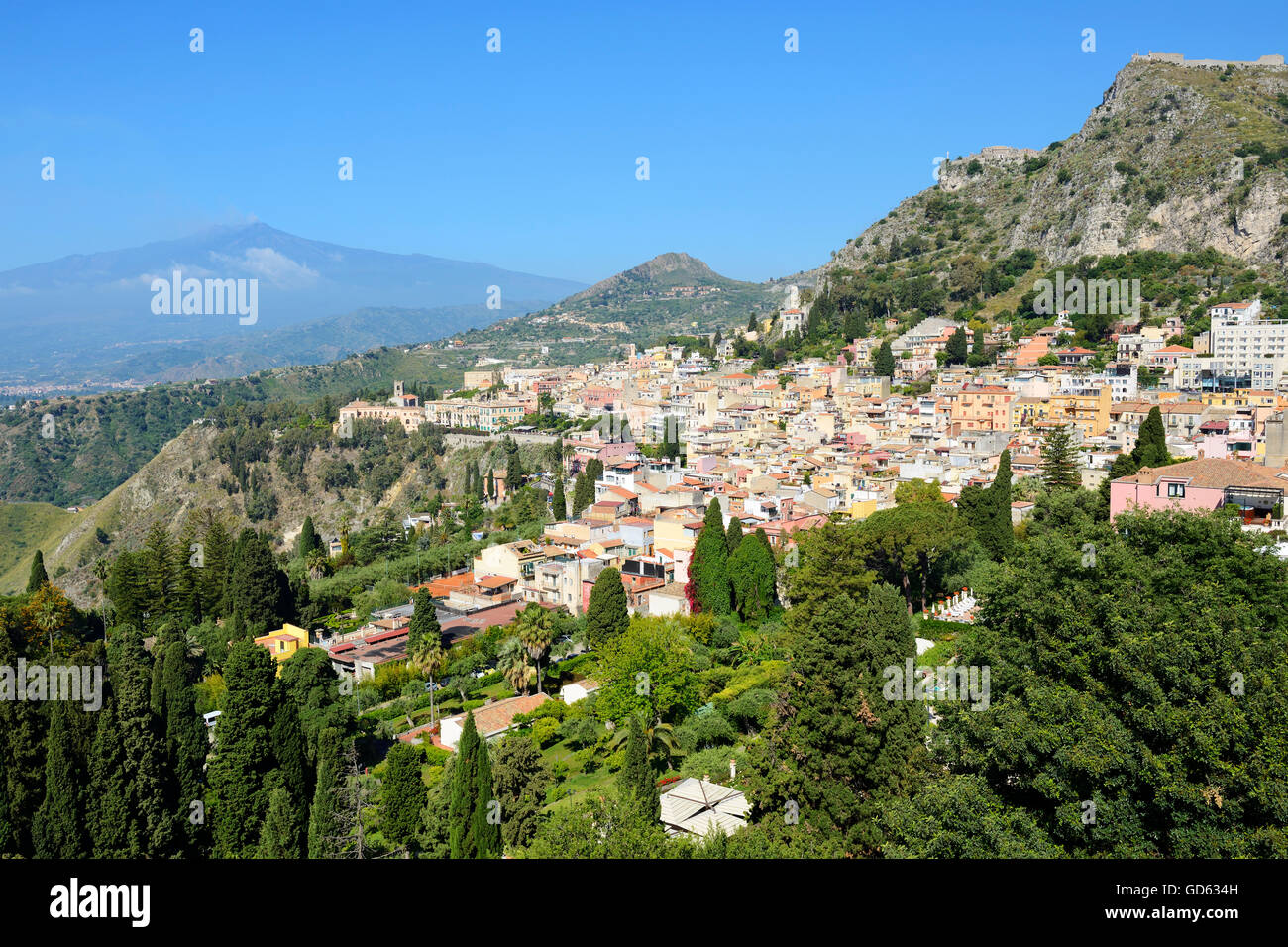 View of hilltop town of Taormina with Mount Etna in background - Taormina, Sicily, Italy - Stock Image