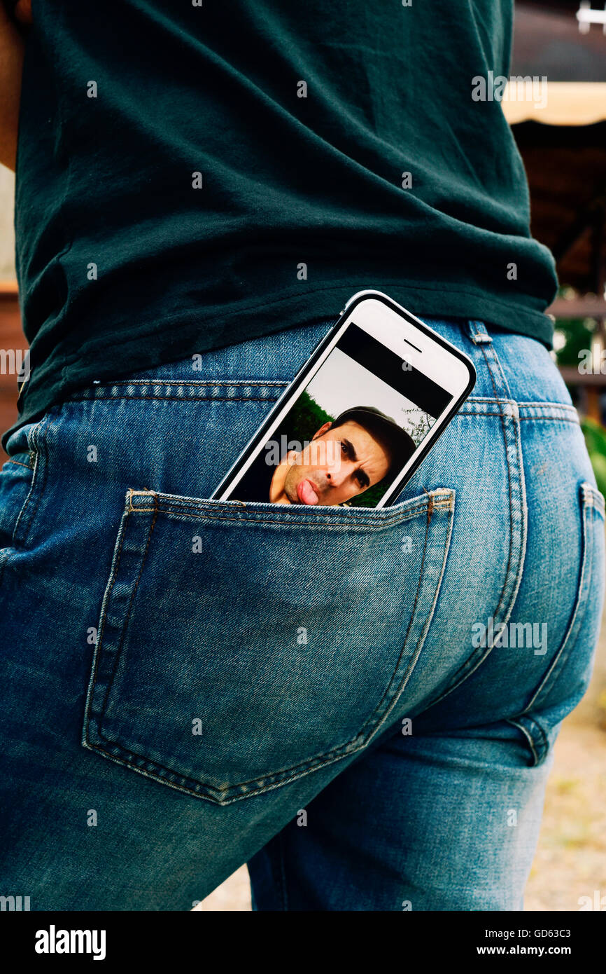 a smartphone with a picture of a young man sticking his tongue out in its screen, taken by myself, placed on the - Stock Image