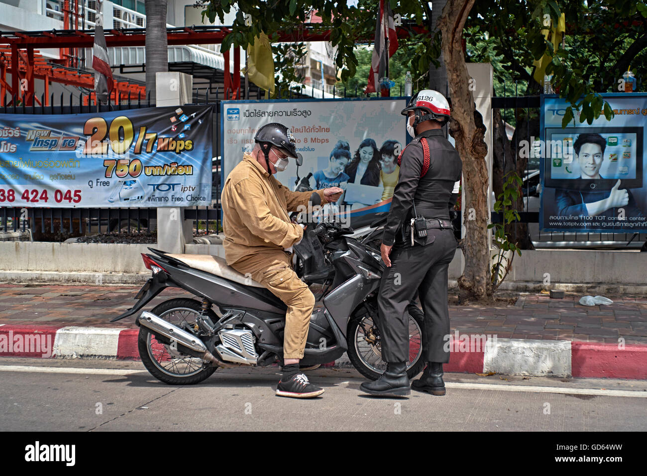 Motorcyclist stopped by Thai police officer for traffic violation. Thailand S. E. Asia - Stock Image