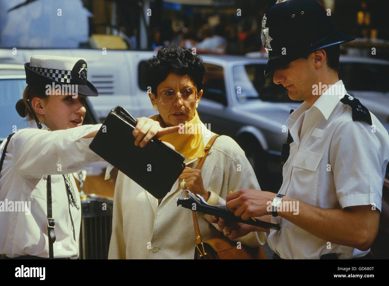 Police officers giving directions to a woman. London. England. UK - Stock Image