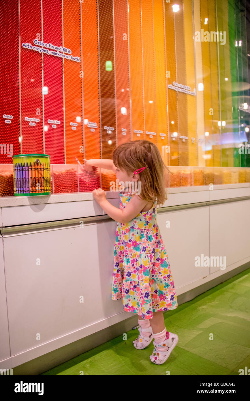 Little girl standing on tiptoe in a colorful art supply store selecting colored wax crayons from a display with - Stock Image
