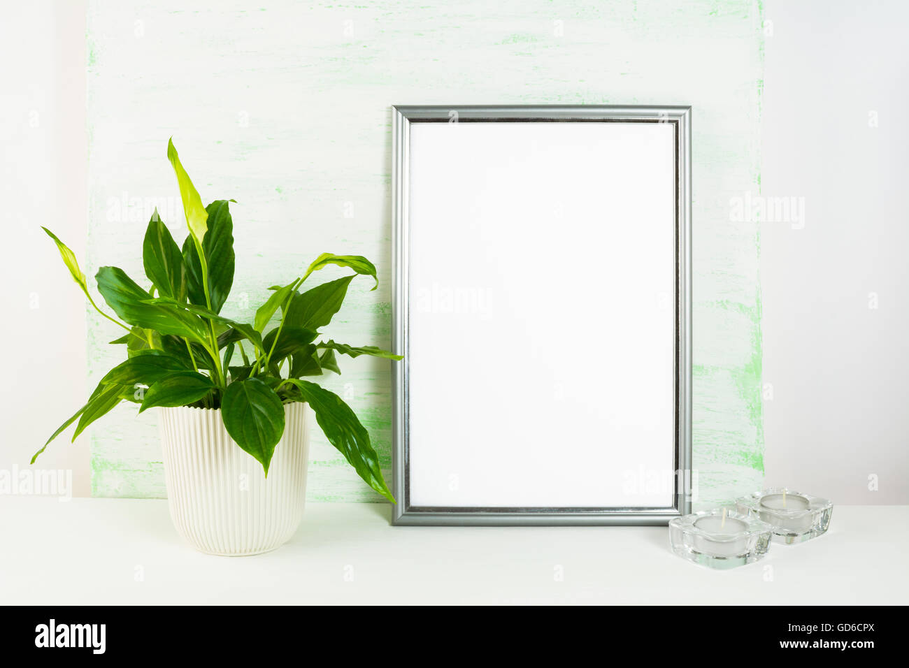 2ee1c260da95 Silver frame mockup with flower pot and candles. Portrait or poster white frame  mockup. Empty white frame mockup for presentatio