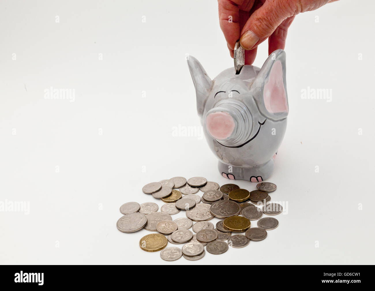 Adding coins to elephant money box - Stock Image