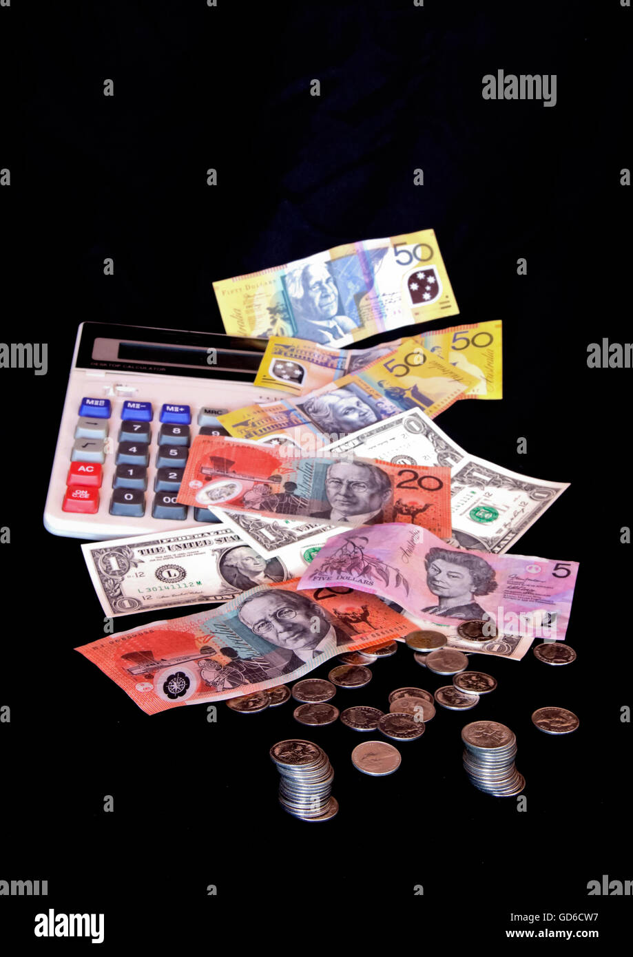 Coins and banknotes isolated on black - Stock Image