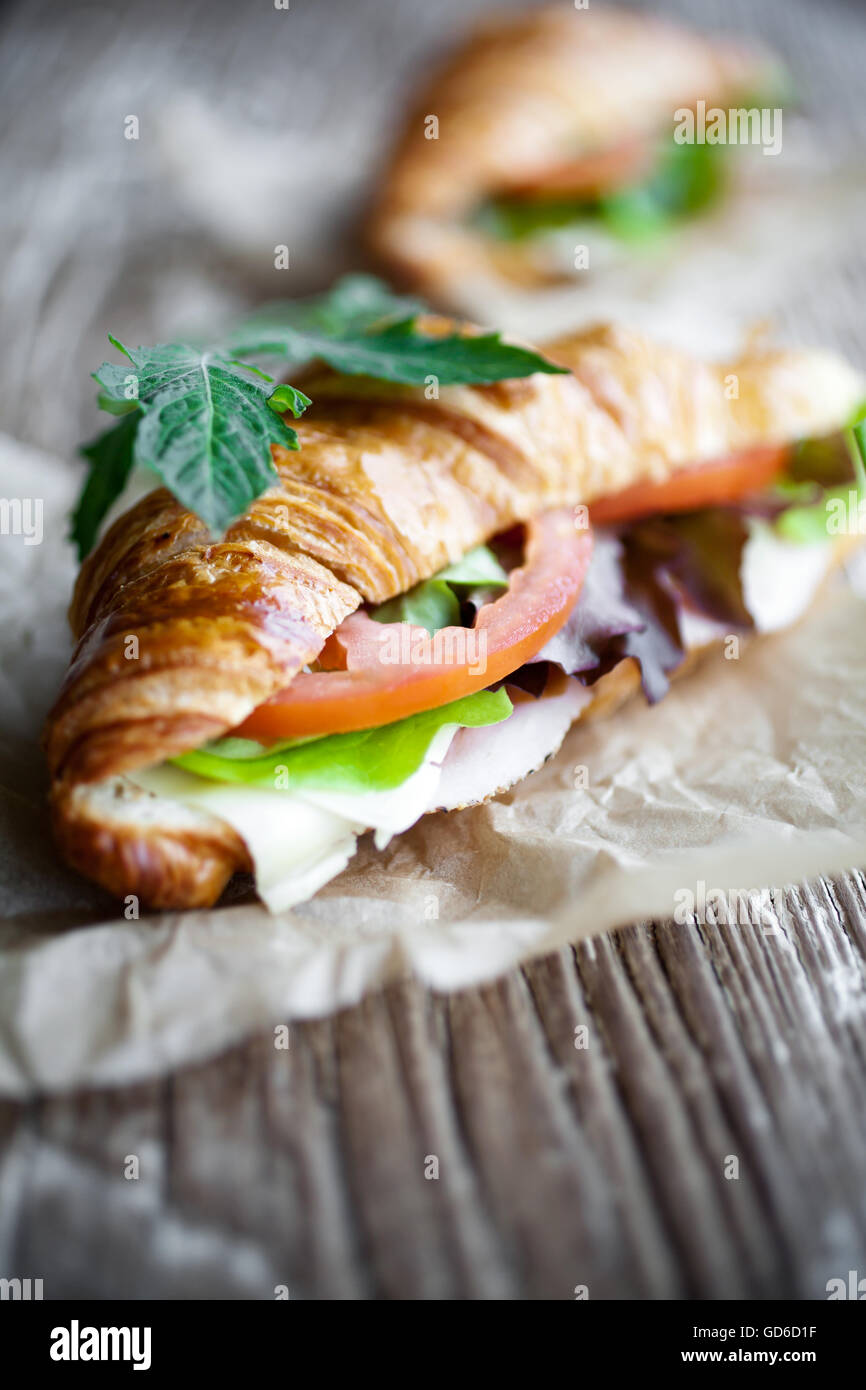 Fresh homemade croissant with ham and salad - Stock Image