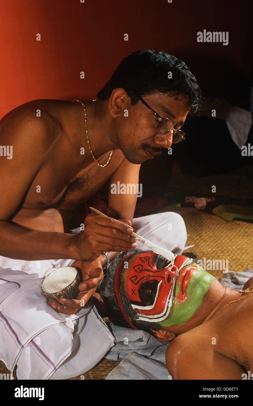Man painting the face of an artiste - Stock Image