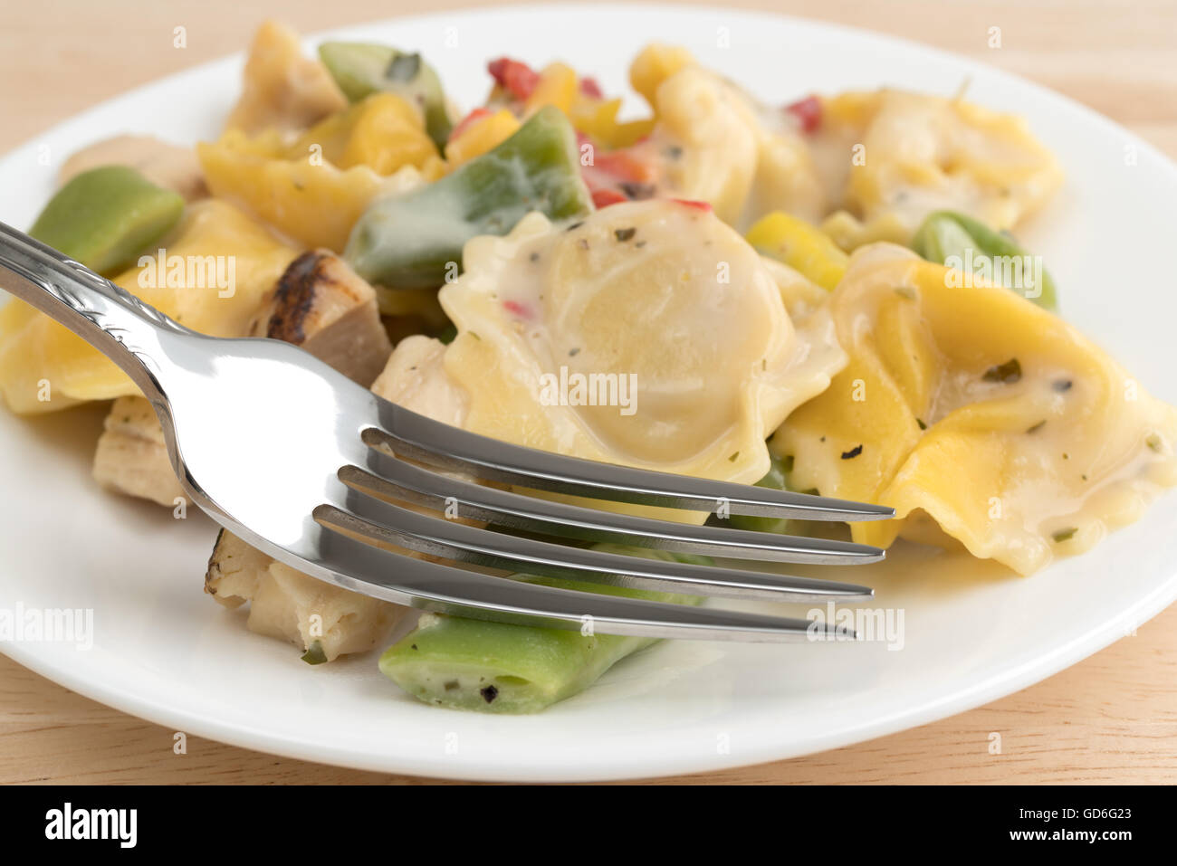 Side close view of a chicken with tortellini and vegetable TV dinner on a white plate with a fork atop a wood table. - Stock Image