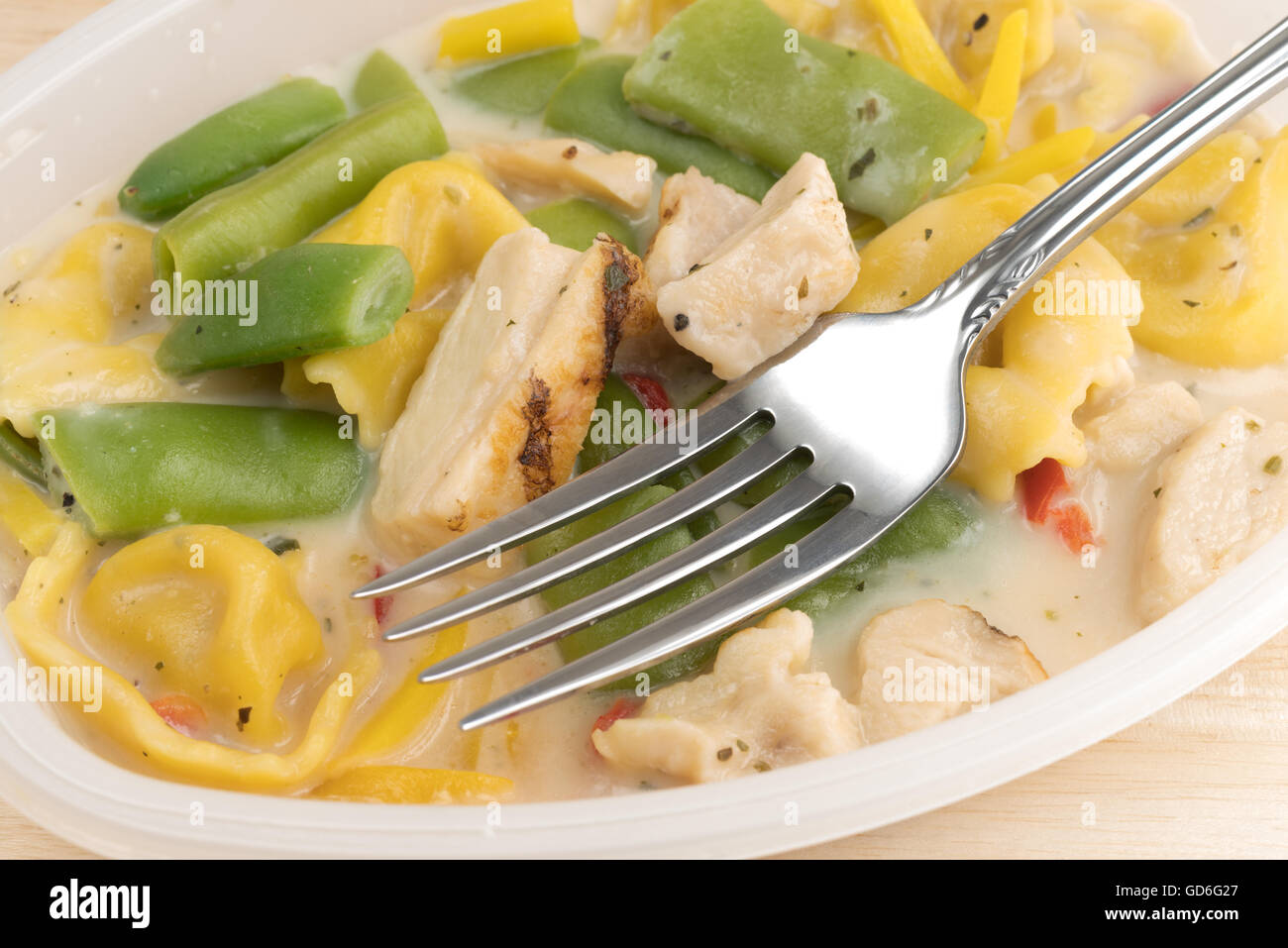 Close view of a chicken with tortellini and vegetable TV dinner in a plastic tray with a fork atop a wood table. - Stock Image