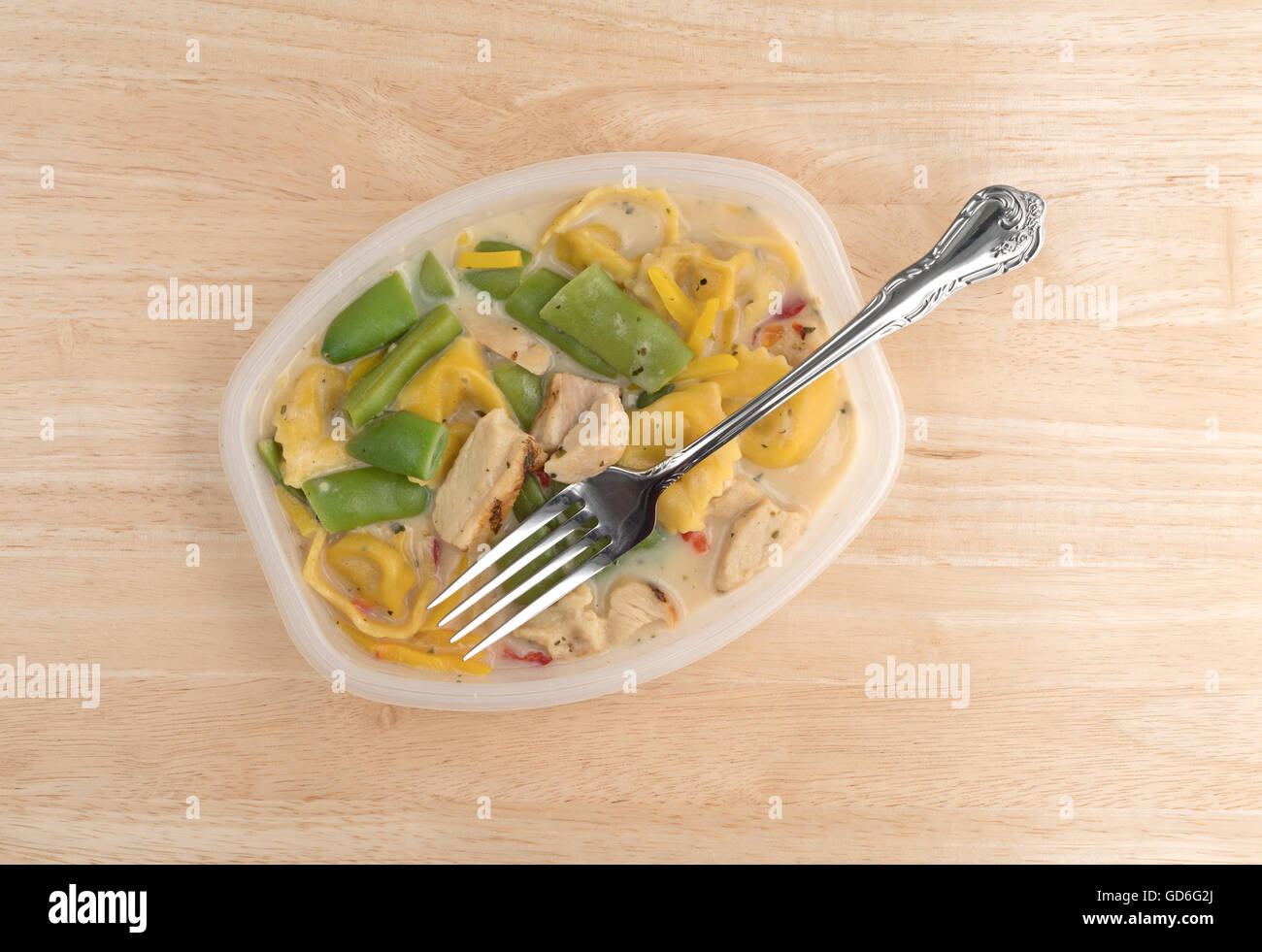 Top view of a chicken with tortellini and vegetable TV dinner in a plastic tray with a fork in the food atop a wood - Stock Image
