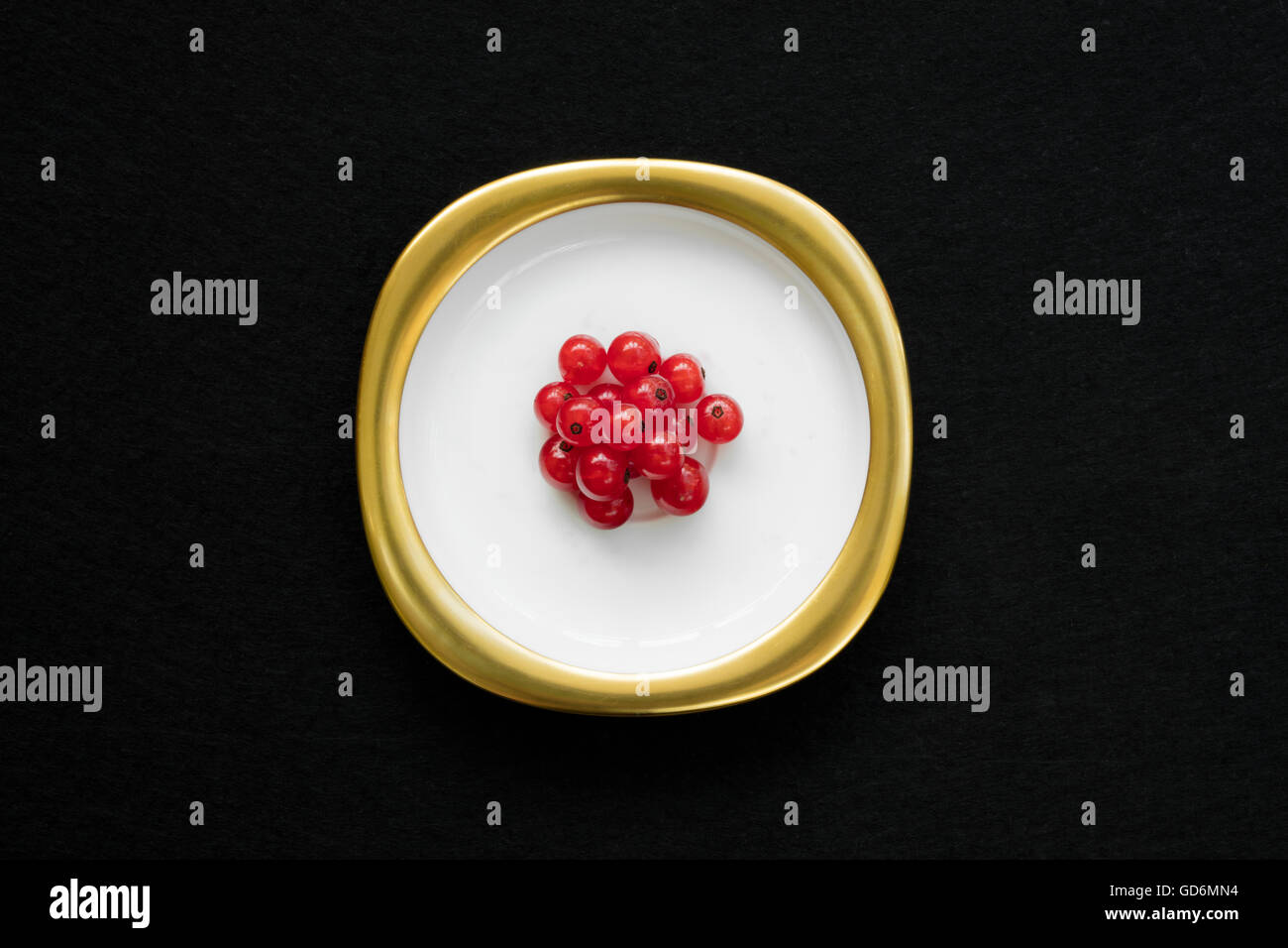 Group of red currants placed on a golden dish with isolated black background. - Stock Image