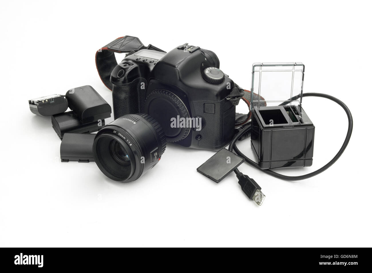 Photographic camera reflex with lens, lithium batteries, SD card and cube to transfer data to PC on white isolated - Stock Image