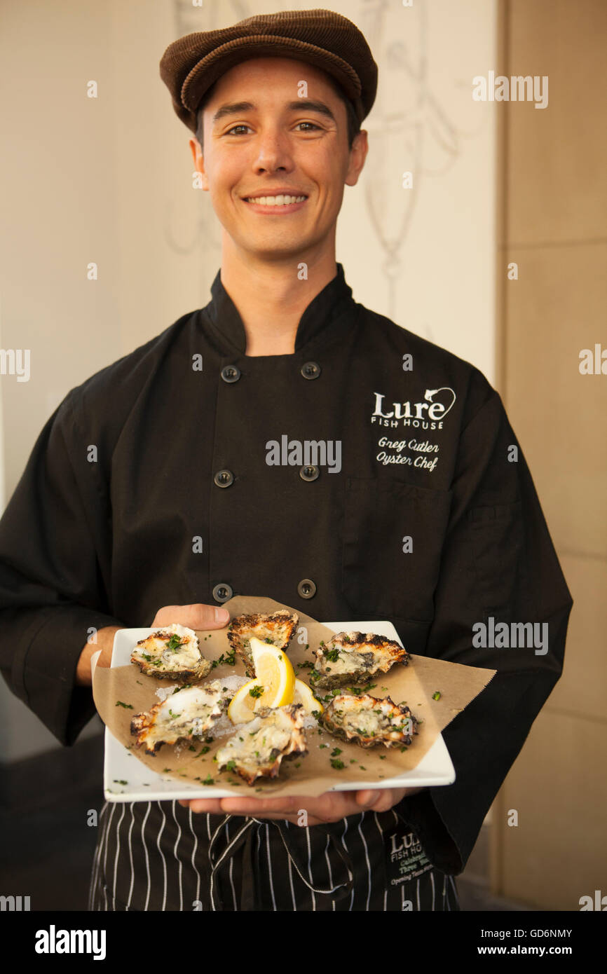 server presents charbroiled oysters, Lure Fish House and Oyster Bar, Santa Barbara, California - Stock Image