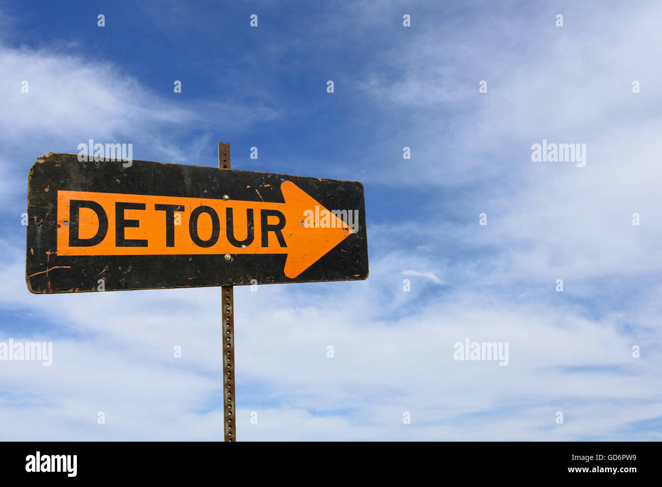 Bold orange and black detour sign with wispy clouds in summer sky. - Stock Image