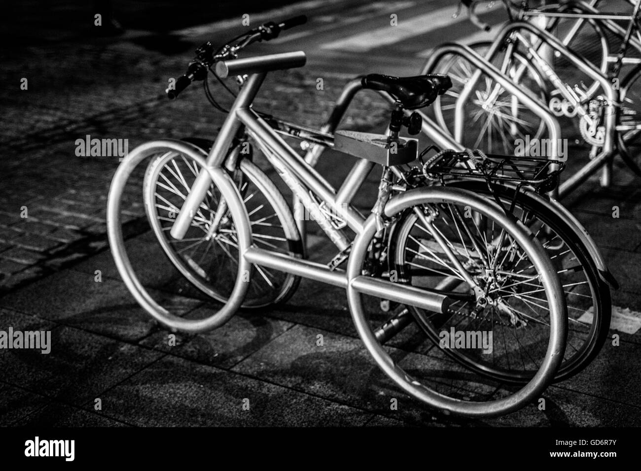 Bicycles Parked In Rack On Footpath - Stock Image