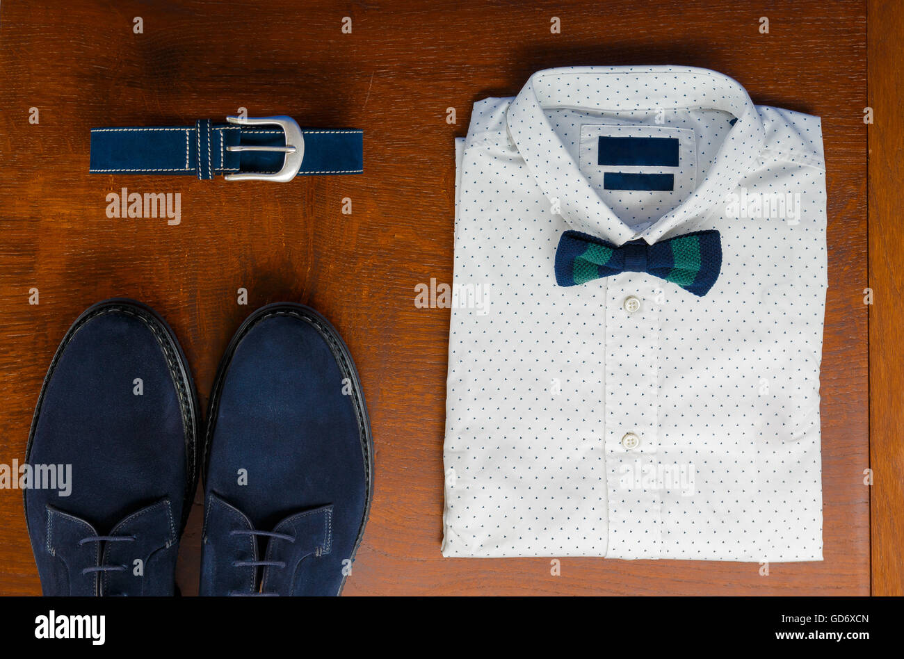 Mens outfits, white polka-dot shirt with with bow tie, blue belt and shoes on brown background. Mens wedding accessory. - Stock Image