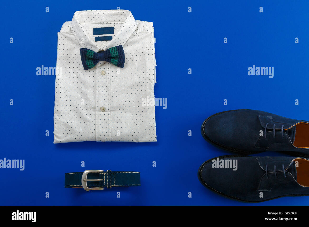 Mens wedding accessory. Mens outfits, white polka-dot shirt with with bow tie, blue belt and shoes on brown background - Stock Image