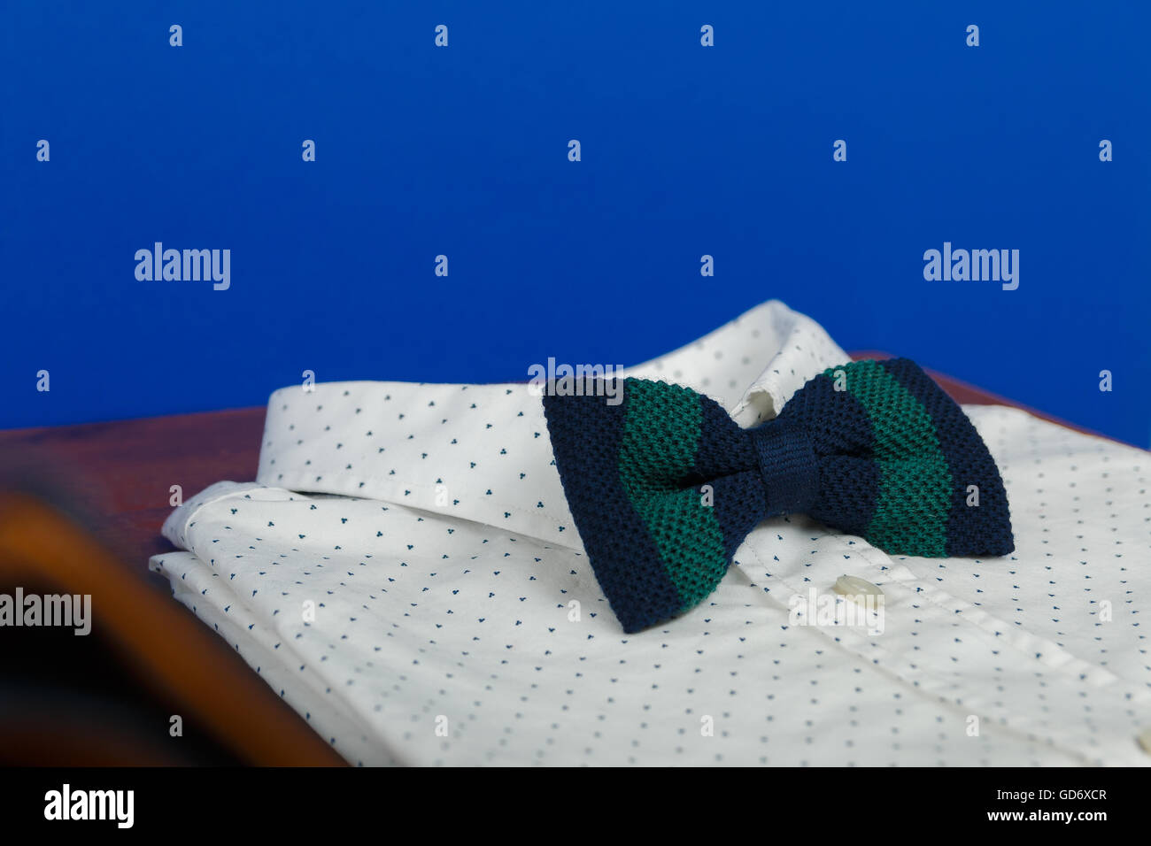Elegant white polka-dot shirt with bow tie in green and blue stripes. - Stock Image