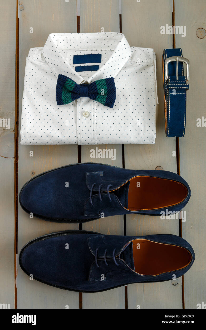 Top view of gentlemanly set. Mens outfits, white polka-dot shirt with with bow tie, blue belt and shoes on grey Stock Photo