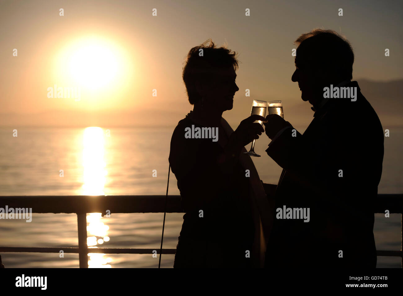 Older couple drinking champaign on a cruise ship at sunset. - Stock Image