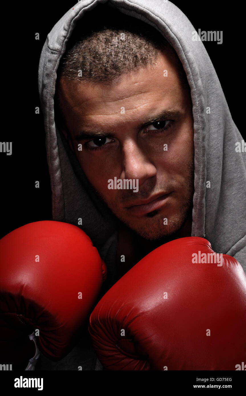 Boxer in a hooded robe and red boxing gloves - Stock Image