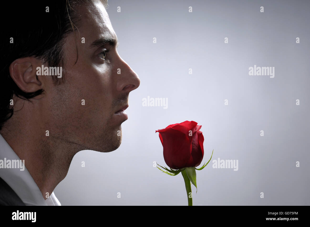 Portrait of a young man with a red rose - Stock Image