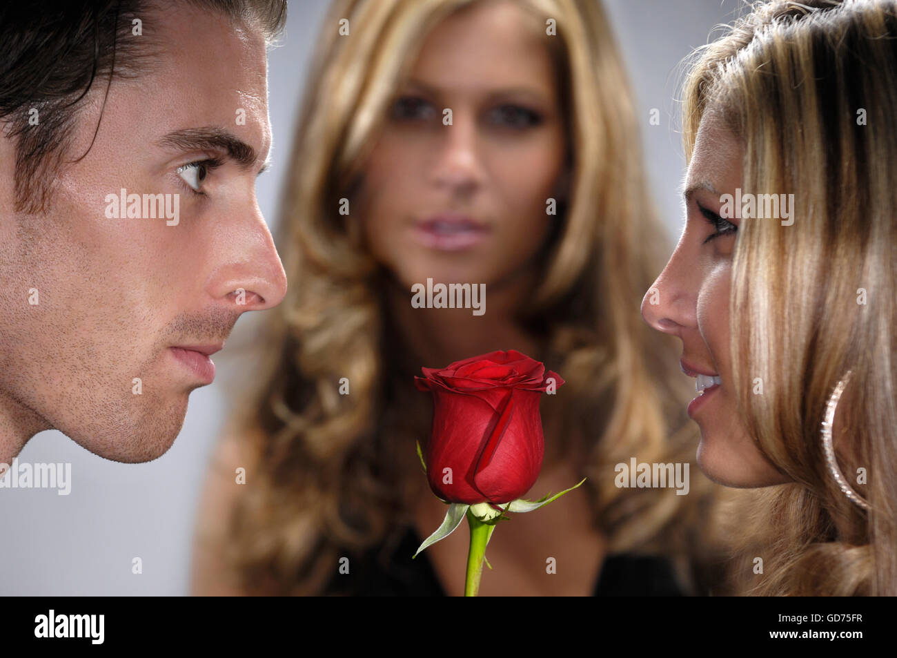 Young man with a red rose facing a young woman, being watched by another - Stock Image
