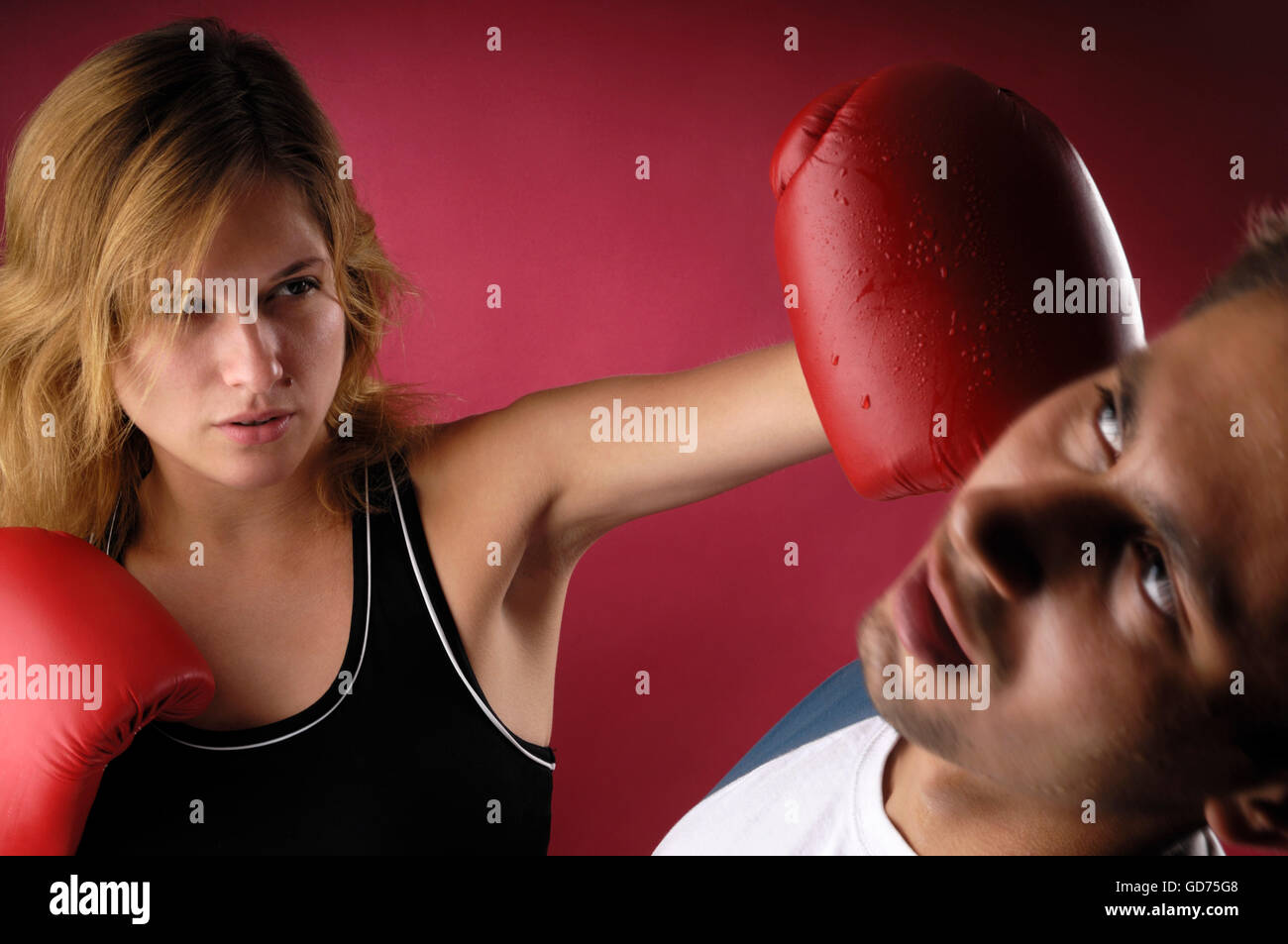 Young female boxer punching a young man on his face, knocking him down - Stock Image